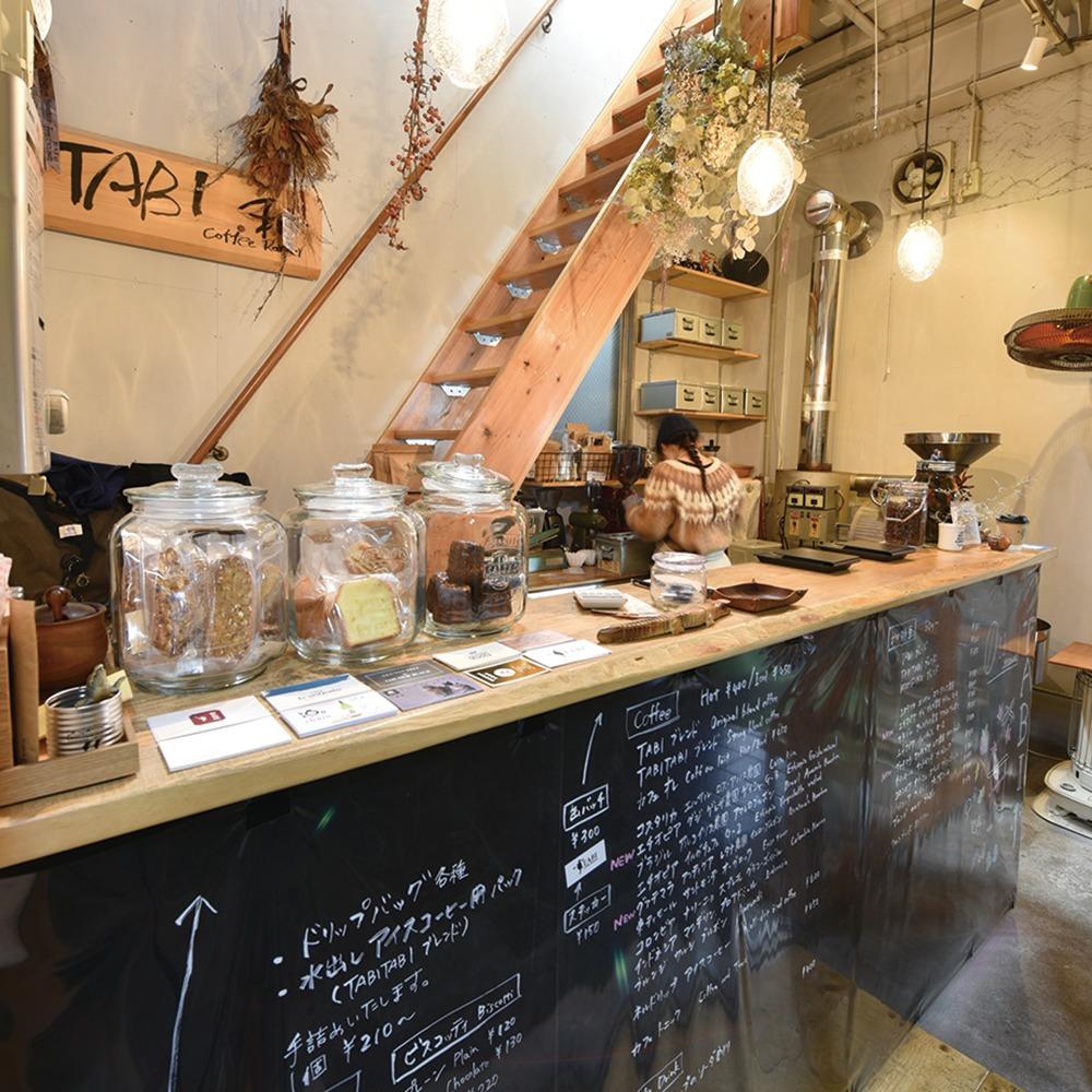 """奈良市、TABI Coffee Roaster、yomiっこ珈琲特集。レトロな市場の中で異彩を放つコーヒースタンド。焙煎暦13年の店主が世界屈指の豆を全てハンドピック、小量焙煎の中煎り~深煎りで、新鮮かつ幅広い年齢層の好みに応える。奥様手焼きのカヌレやビスコッティと共に、仕事や""""旅""""の一服に。タビコーヒー ロースター。奈良市椿井町5  椿井市場内"""